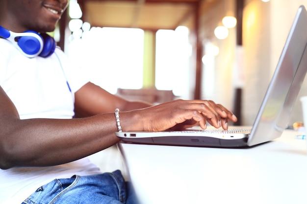 Concentração total. parte de close-up de um jovem africano usando um laptop enquanto está sentado em seu local de trabalho