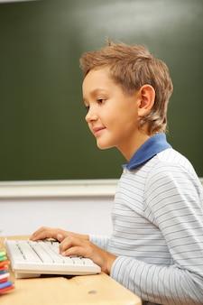 Concentrada do menino com o teclado do computador