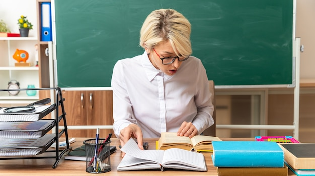 Concentrada jovem loira professora usando óculos, sentada na mesa com as ferramentas da escola na sala de aula, pegando o bloco de notas, mantendo a mão no livro aberto, olhando para o livro