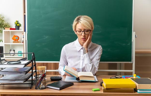 Concentrada jovem loira professora usando óculos, sentada na mesa com o material escolar na sala de aula, lendo o livro, mantendo as mãos no rosto