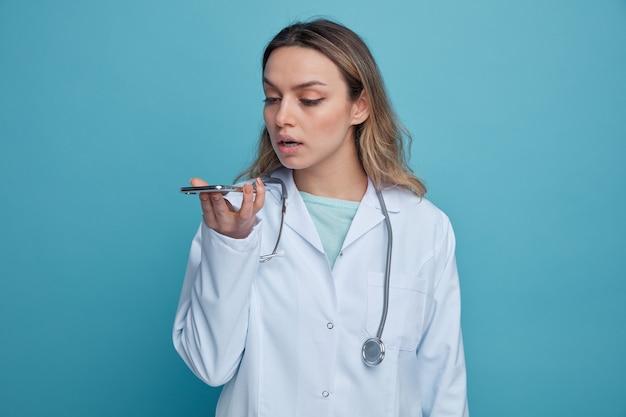 Concentrada jovem médica vestindo bata médica e estetoscópio pendurado no pescoço segurando e olhando para o telefone celular, falando pelo microfone