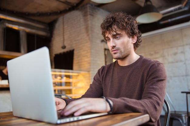 Concentrado bonito atraente encaracolado sério homem em um moletom marrom sentado em um café e usando um laptop