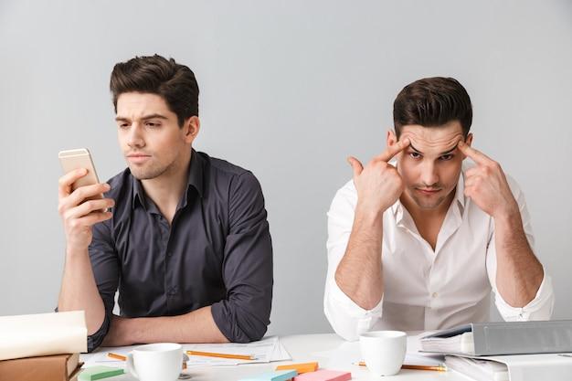 Concentrado de dois jovens homens de negócios usando telefone celular.