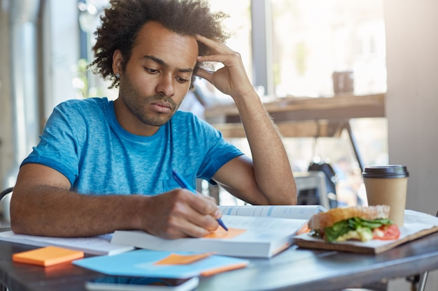 Concentrado estudante universitário afro-americano sério com barba fazendo as tarefas de casa, preparando-se para a aula de espanhol, escrevendo novas palavras do texto em post-its durante o café da manhã no café