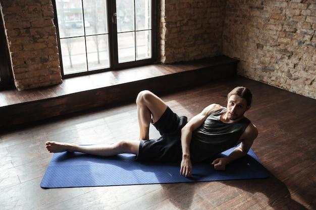 Concentrado forte esportista no ginásio encontra-se no chão.