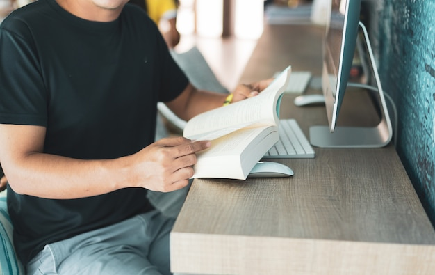 Concentrado homem asiático lendo livro na cafeteria