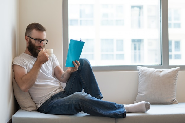 Concentrado homem de óculos, bebendo café enquanto lê o livro