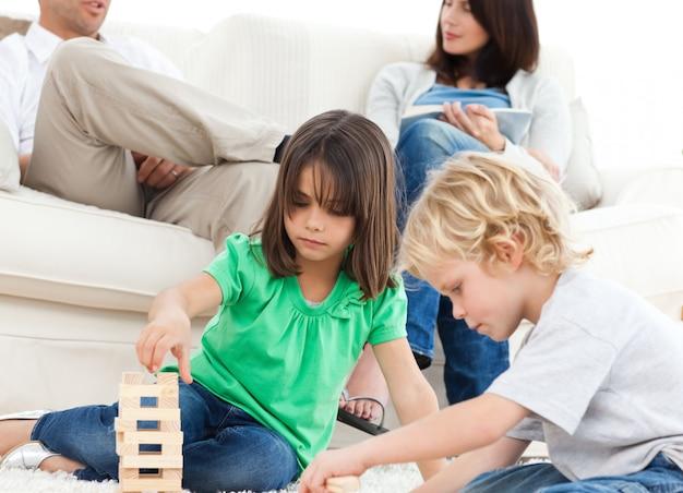 Concentrado irmão e irmã brincando com dominós no chão
