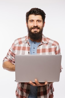 Concentrado jovem barbudo de óculos, vestido com camisa, usando laptop isolado sobre uma parede branca.