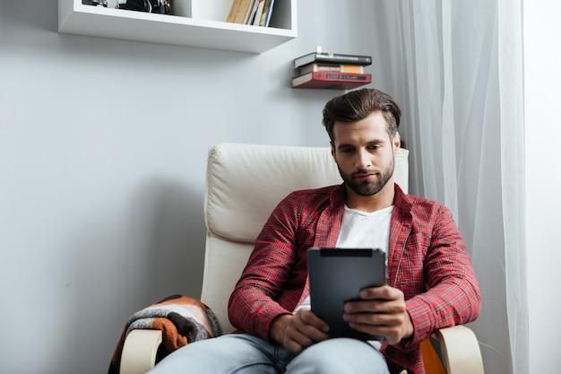 Concentrado jovem barbudo usando computador tablet