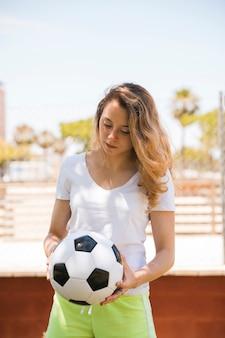 Concentrado jovem com bola de futebol