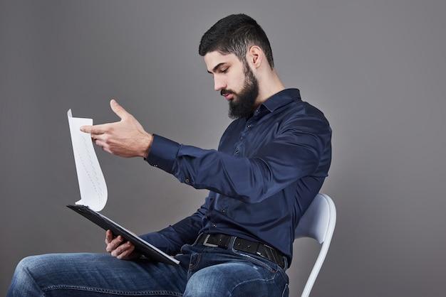 Concentrado jovem empresário atraente na camisa azul, planejamento e escrita na área de transferência