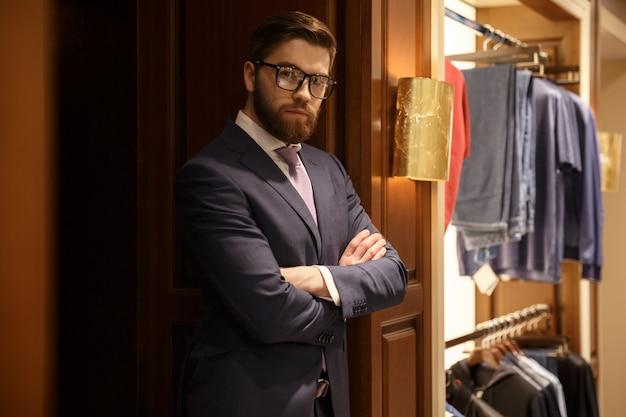 Concentrado jovem empresário barbudo em pé dentro de casa Foto gratuita