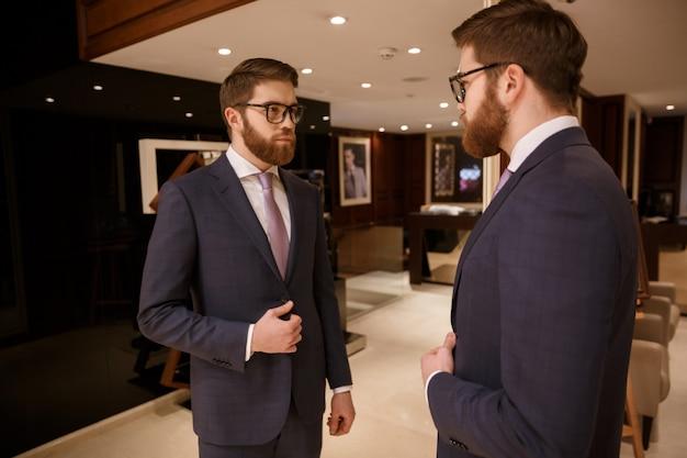 Concentrado jovem empresário barbudo em pé dentro de casa