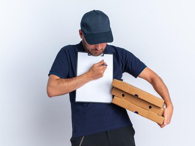 Concentrado jovem entregador caucasiano de uniforme azul e boné segurando pacotes de pizza e prancheta com o queixo olhando para a prancheta apontando caneta isolada na parede branca