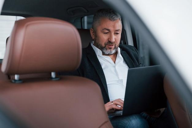 Concentrado no trabalho. trabalhando em uma traseira do carro usando o laptop de cor prata.