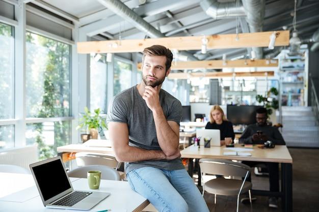 Concentrado pensando jovem sentado na mesa no escritório