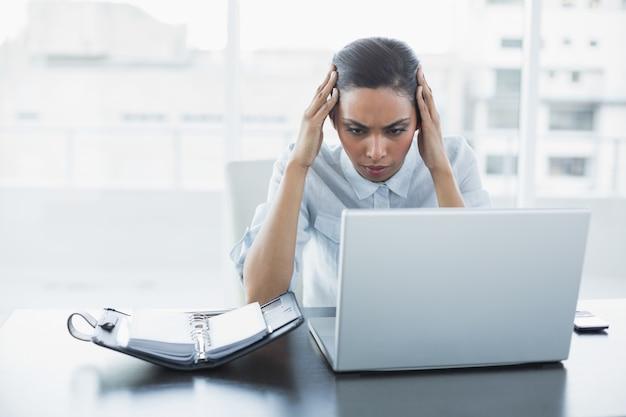 Concentrando a jovem empresária trabalhando em seu laptop sentado em sua mesa