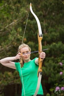 Concentrando mulher loira praticando tiro com arco