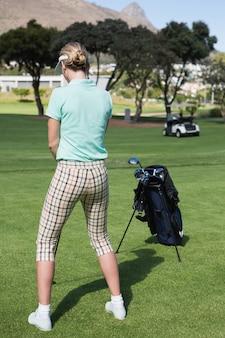 Concentrando-se feminino golfista teeing fora em um dia ensolarado no campo de golfe