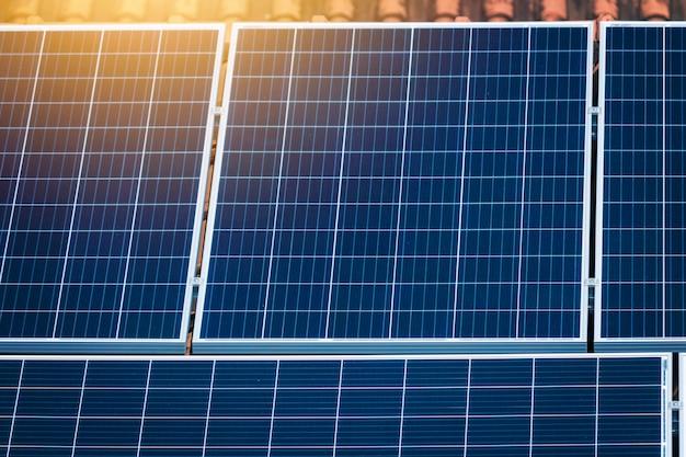 Concentre-se em painéis solares no telhado vermelho. energia solar fotovoltaica zoom imagem do conceito de instalação.