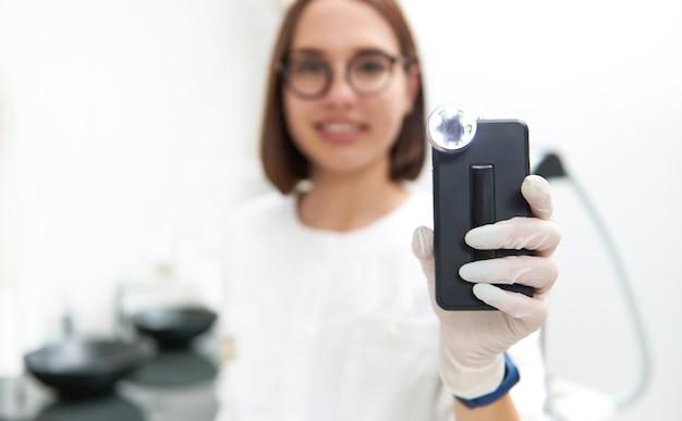 Concentre-se em um dermatoscópio para analisar e examinar manchas e crescimentos de pele e neoplasias nas mãos do médico. conceito de detecção precoce do câncer