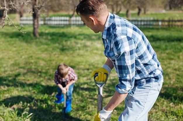 Concentre-se em um homem maduro olhando para seu filho pequeno, ambos vestindo uma camisa xadrez e cavando a terra em um jardim familiar