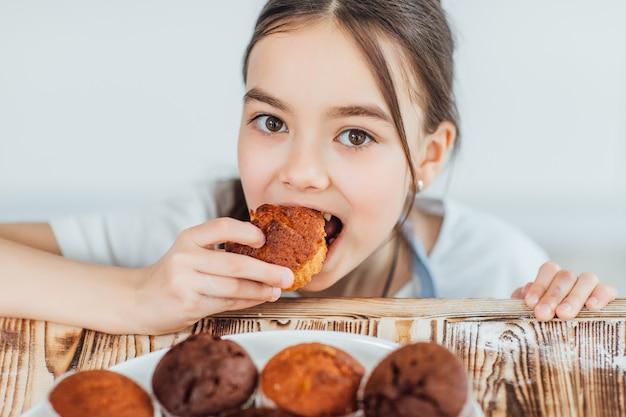 Concentre-se em uma garotinha mordendo cupcakes
