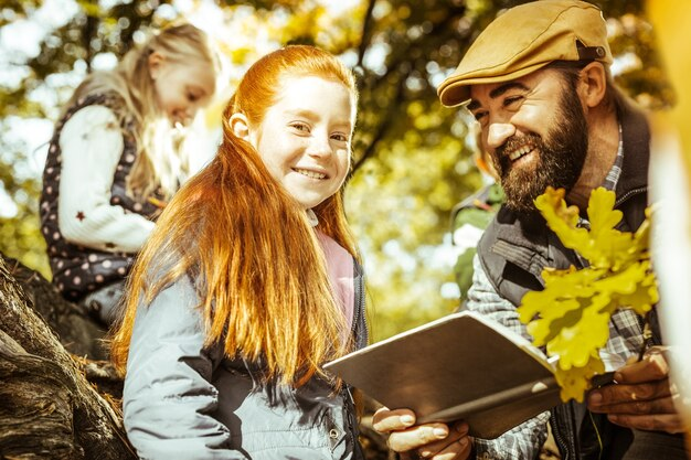 Concentre-se em uma pequena menina ruiva e seu professor dando uma aula na floresta ensolarada em um dia bom