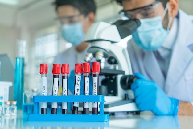 Concentre-se na amostra de sangue de covid-19. cientistas da equipe pesquisando o vírus em microscópio em laboratório