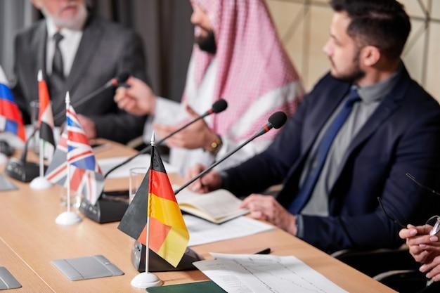 Concentre-se na bandeira da mesa alemã durante a reunião, foto de close-up. executivos cortados sentados em uma entrevista coletiva, reunidos sem vínculos