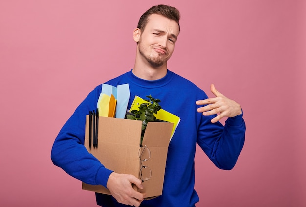 Concentre-se na caixa. cara legal hipster de suéter escuro está abraçando a caixa demitida