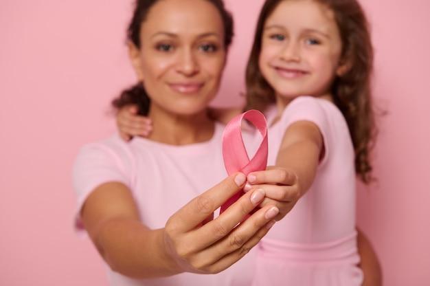 Concentre-se na fita de cetim rosa nas mãos de duas gerações de mulheres, mãe e filha posando em fundo rosa, mostrando apoio e solidariedade aos pacientes sobreviventes de câncer. dia mundial da luta contra o câncer
