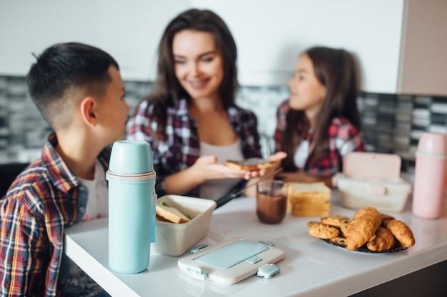 Concentre-se na garrafa térmica na mesa, atrás da jovem mãe e seu filho fazendo sanduíche escolar para o almoço