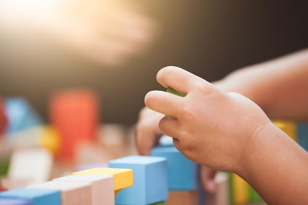 Concentre-se na mão da criança brincando com blocos de madeira coloridos no tom de cor vintage