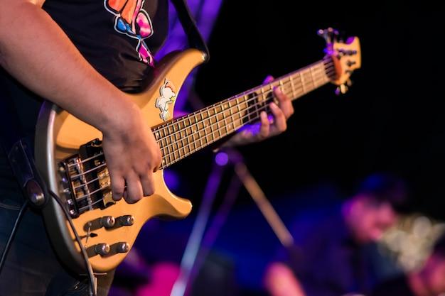 Concentre-se na mão que está tocando a guitarra de madeira no palco.