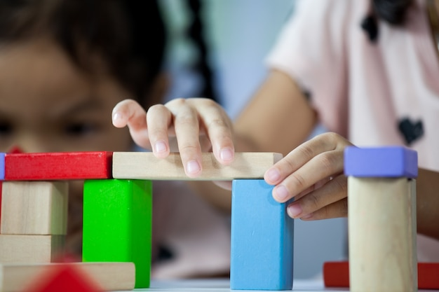 Concentre-se nas mãos de uma criança pequena e fofa brincando com blocos de madeira coloridos na sala