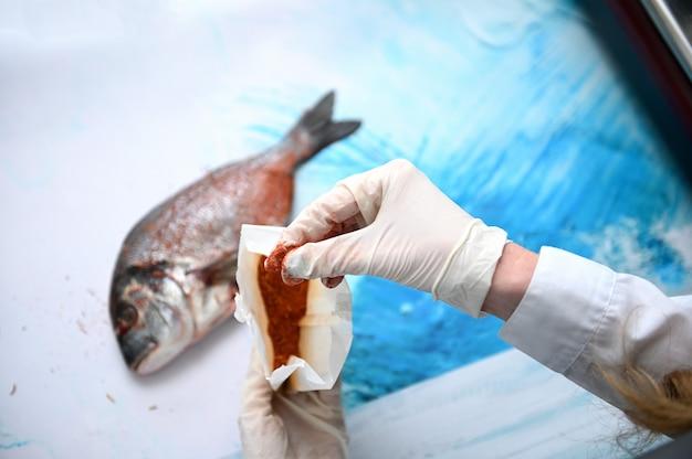Concentre-se nas mãos enluvadas do chef. o peixeiro segura um saco de papel com especiarias e espalha o tempero no peixe dourado na mesa da loja de frutos do mar