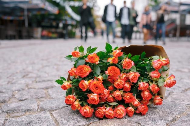 Concentre-se no buquê de rosas em papel ofício na rua de pavimentação cinza