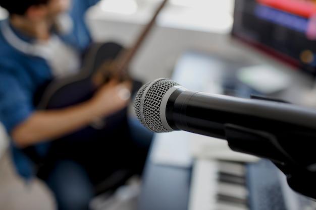 Concentre-se no microfone. homem toca guitarra e produz trilha sonora eletrônica ou faixa em projeto em casa. arranjador de música masculina, compondo a música no piano midi