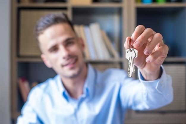 Concentre-se no molho de chaves de um apartamento de casa na mão de um homem sorridente. retrato borrado de um corretor de imóveis profissional confiante que oferece uma nova unidade de habitação ao potencial comprador. fechar-se