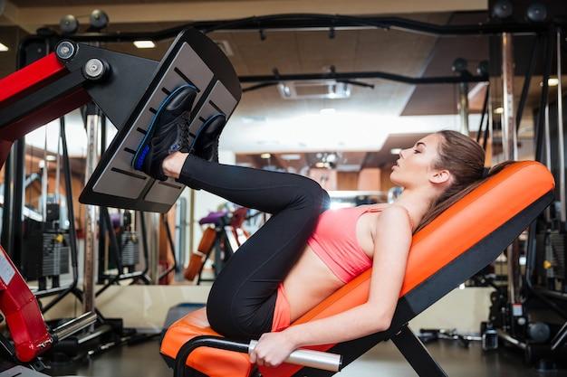 Concentrou-se em uma jovem e forte desportista fazendo exercícios para os músculos das pernas na academia