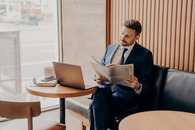 Concentrou-se no jovem empresário rico de terno azul e camisa branca lendo notícias sobre sua empresa iniciante no jornal local enquanto está sentado sozinho em um café confortável com um laptop na frente dele