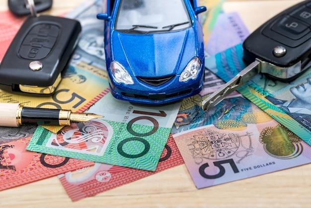 Concepção de 'compra ou aluguel' com carro de brinquedo e dólares australianos