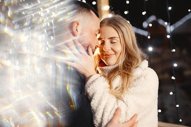 Concepção de férias de inverno. retrato noturno ao ar livre do jovem casal. posando na rua da cidade europeia.