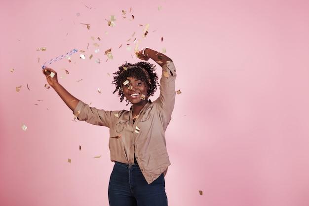 Concepção de festa. jogando o confete no ar. mulher afro-americana com fundo rosa atrás