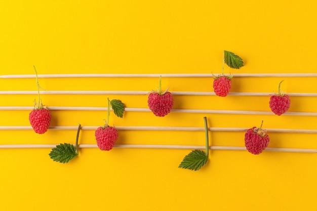 Concepção de notas musicais. notas musicais de madeira e framboesas