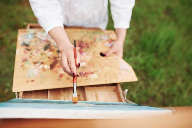 Concepção de pintura. foto da mão de uma mulher com pincel vermelho
