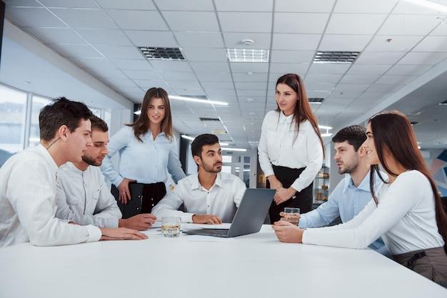 Concepção de sucesso. grupo de jovens freelancers no escritório tem conversa e sorrindo