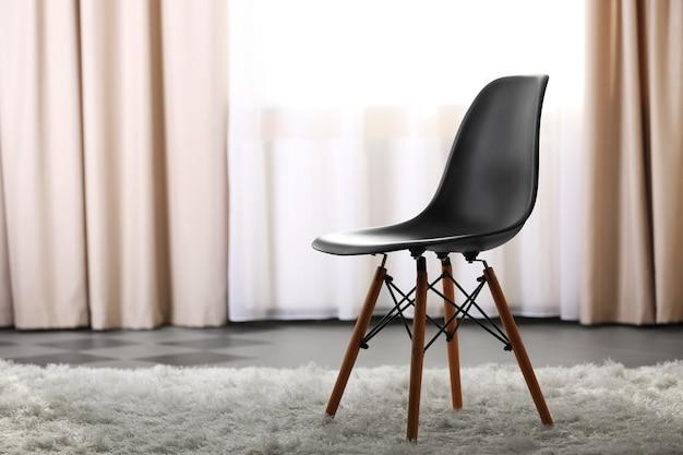 Concepção elegante com cadeira preta na sala de luz
